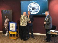 Past HVC President Tom Pluess whom sponsored Paul Graham is pinning the SAR Rosette on him.