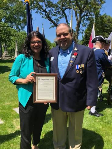 Rep. Tlaib presents the Congressional Record on Robinson to MISSAR Secretary Elijah Shalis.