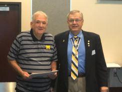 Registrar Al Treppa accepts his son Martin Treppa's Military Service Medal from President Petres.