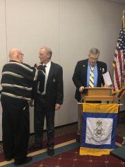 New Member Jon Luker is pinned his SAR membership rosette by Genealogist and Past President Tom Pleuss.